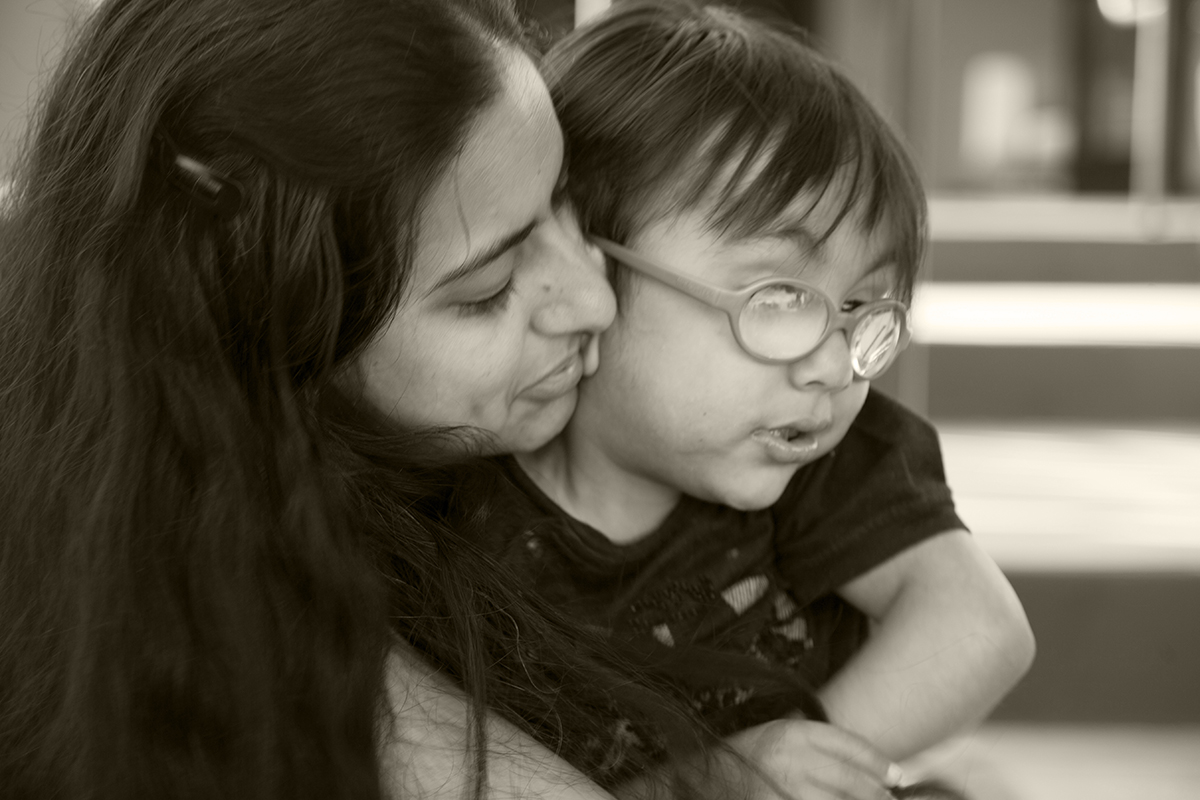 Mom hugging child with glasses